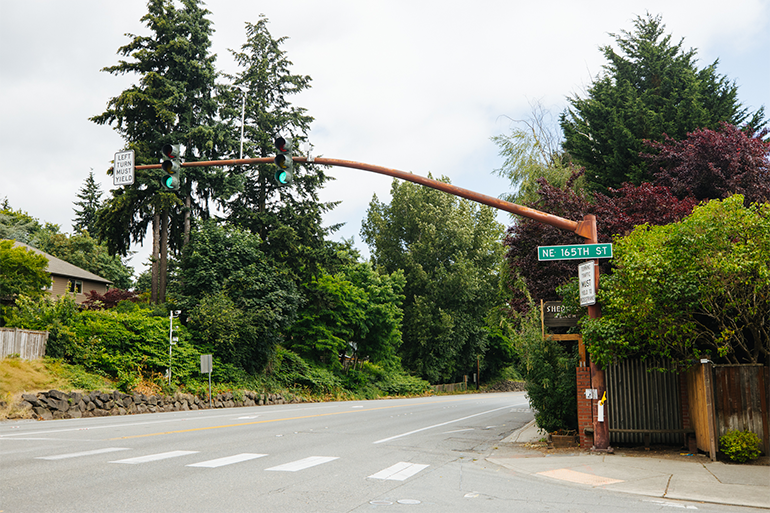 """A photo shows the intersection of SR 522 and NE 165th Street in Lake Forest Park. A traffic light over the roadway is green. Adjacent to the roadway and above the sidewalk, a sign says """"Sheridan Beach."""" Many green trees line the roadway and sidewalk."""